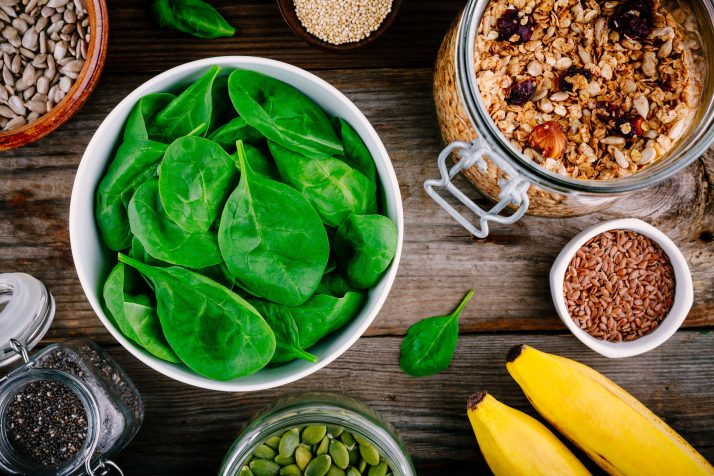 Ingredients for green spinach smoothies: bananas, granola, chia seeds on wooden background