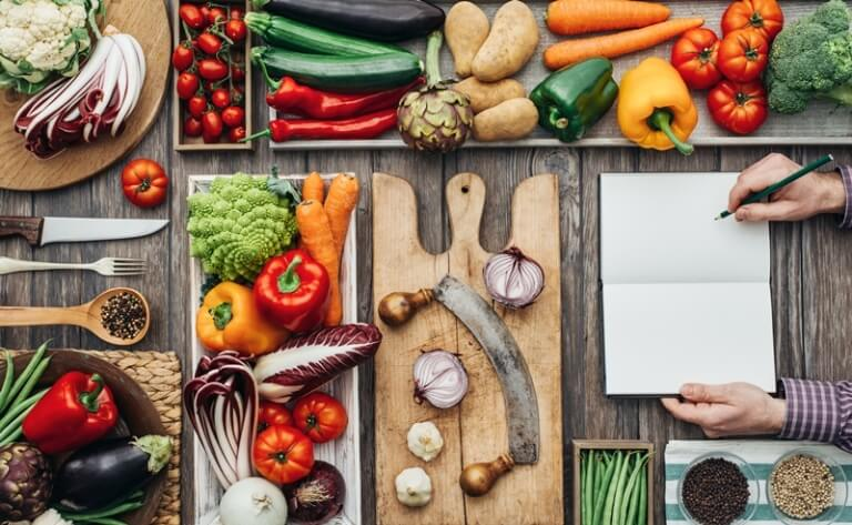 Free Weight Loss Calculator: How Many Calories Should I Eat? vegetables and knife and woman taking notes in notebook