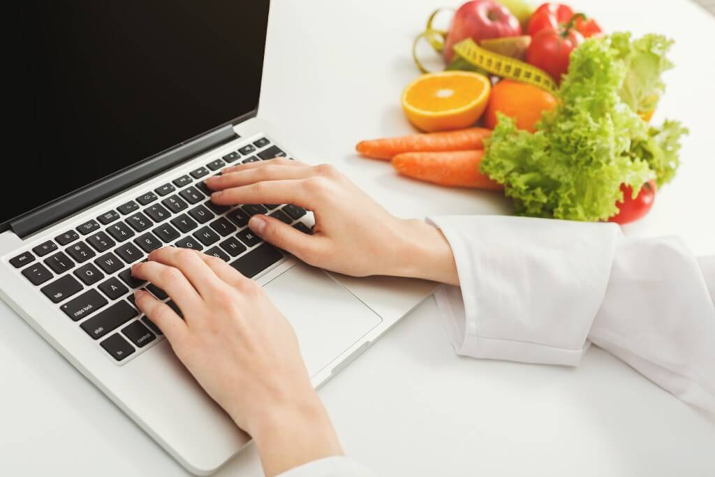 Free Weight Loss Calculator: How Many Calories Should I Eat? woman typing on laptop next to tape and fruits and vegetables