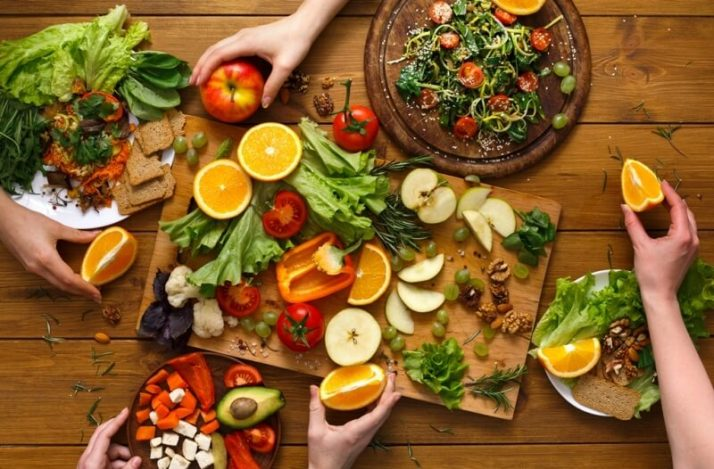 Going Vegan?; Dinner table, women eat healthy food at home kitchen