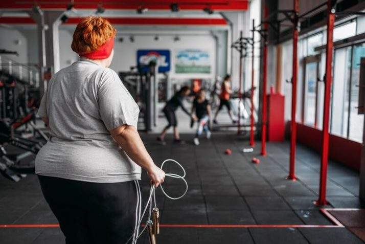 Worldwide Obesity Statistics, Facts & Trends; Fat sweaty woman, fit training with rope in gym