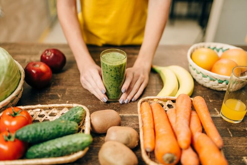 Going Vegan?; Female hands with cocktail of fruit and vegetables, green smoothie