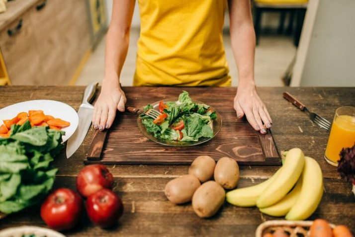 Going Vegan?; Female person cooking, healthy eco food preparing, fruits and vegetables