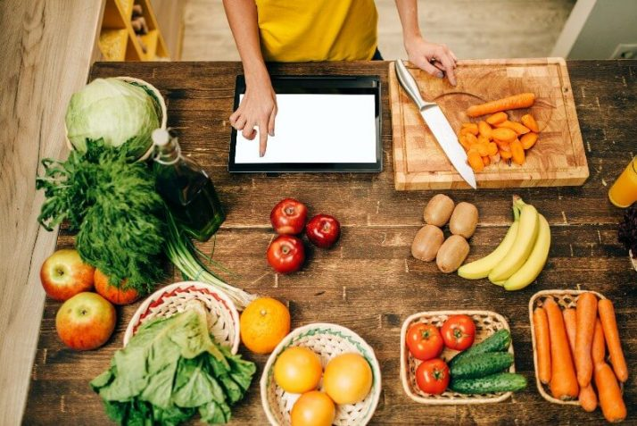 Going Vegan?; Female person cooking on the kitchen, eco food, reading computer