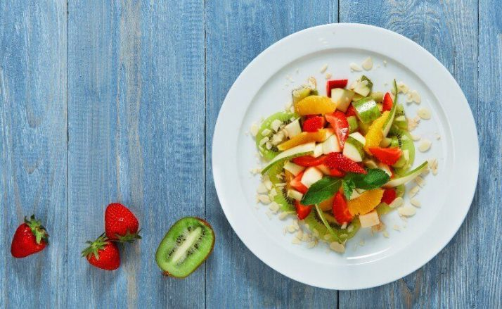 Paleo vs Vegan? Why A Pegan Diet Is Your Best Option; Fruit salad closeup, vegan food kiwi strawberries