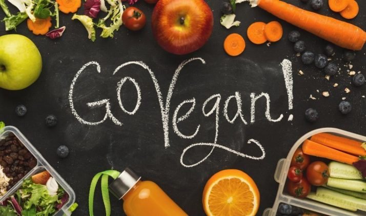 Going Vegan; Lunch boxes filled with healthy food on black board, go vegan