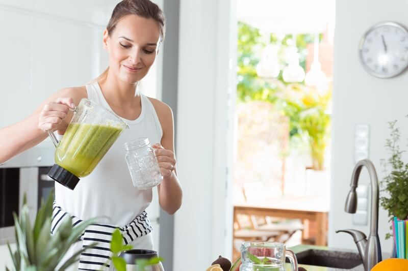 189 Smoothie Ingredients List: Calories, Protein, Carbs, Fat; woman pouring smoothie into jar from blender