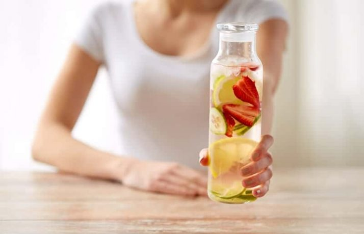 How To Lose 10 Pounds In 1 Week: 3 Step Plan; close up of woman with fruit water in glass bottle