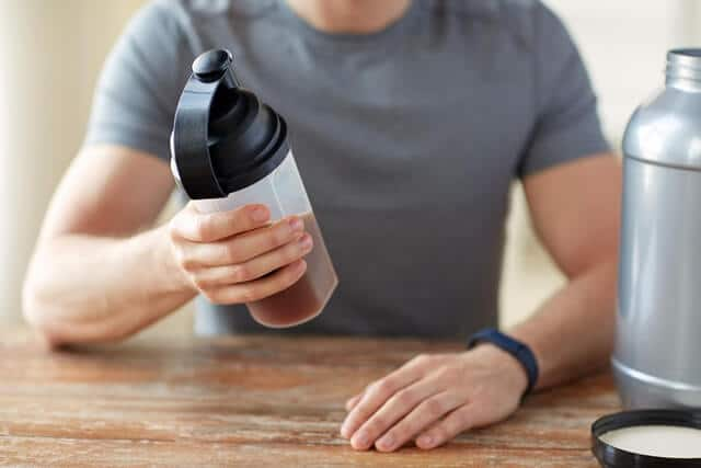 man with protein shake bottle and jar