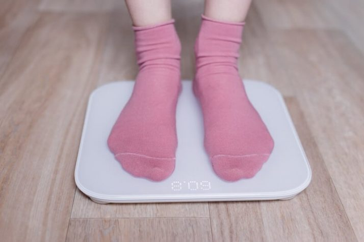 How To Lose 10 Pounds In 1 Week: 3 Step Plan; woman measuring her weight on a modern smart scales