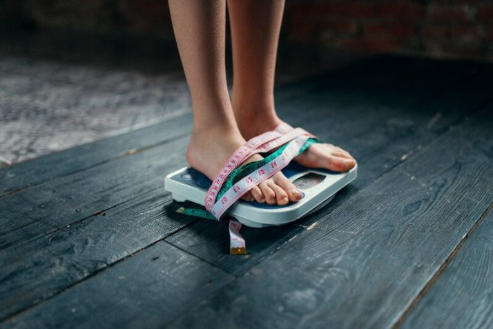 How To Lose 10 Pounds In 1 Week: 3 Step Plan Womans feet on the scales tied with measuring tape