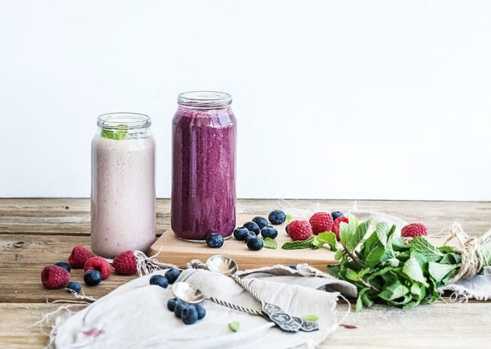 The Ugly TRUTH About Meal Replacement Shakes; Fresh healthy smoothie with blueberries, raspberries in glass jars and mint