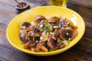 34 High Protein Vegetables You Probably Already Eat; Fried mushrooms shiitake with green onion on wooden background. Chinese food.