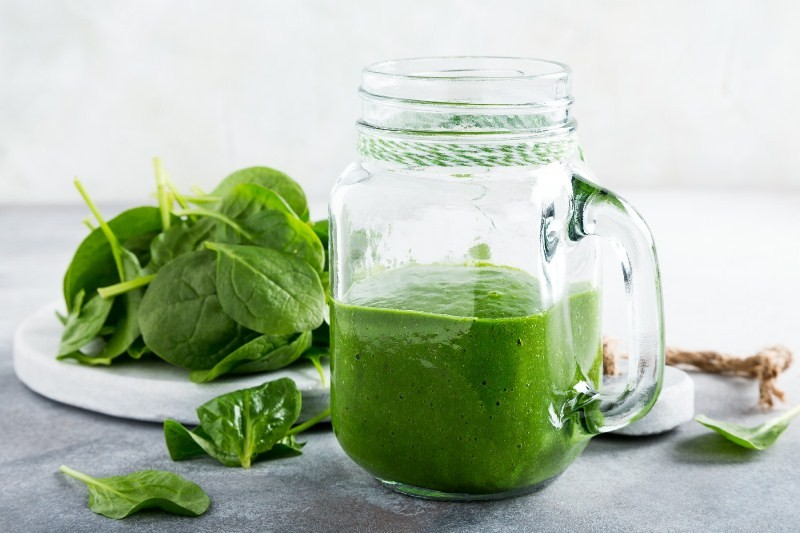 17 Surprising Spinach Nutrition Facts & Health Benefits; Healthy green smoothie with spinach in glass jar
