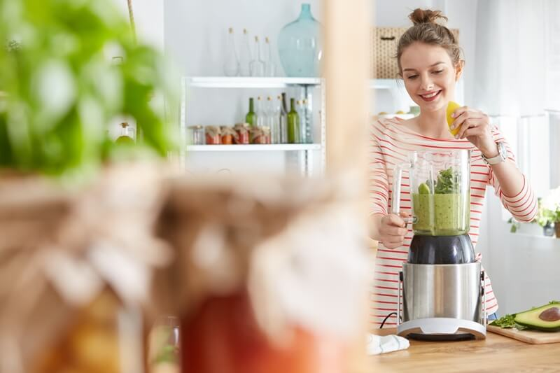 3 Vegetables That Provide ALL Your Essential Nutrients (With Only 450 Calories); Woman making vegetable green smoothie in a blender