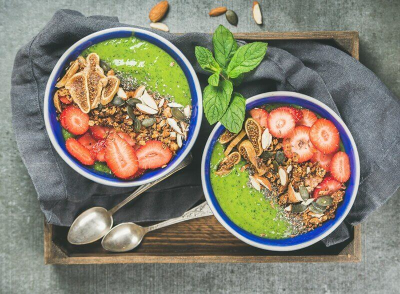 green smoothie breakfast bowls with granola, fruit, seeds, berries