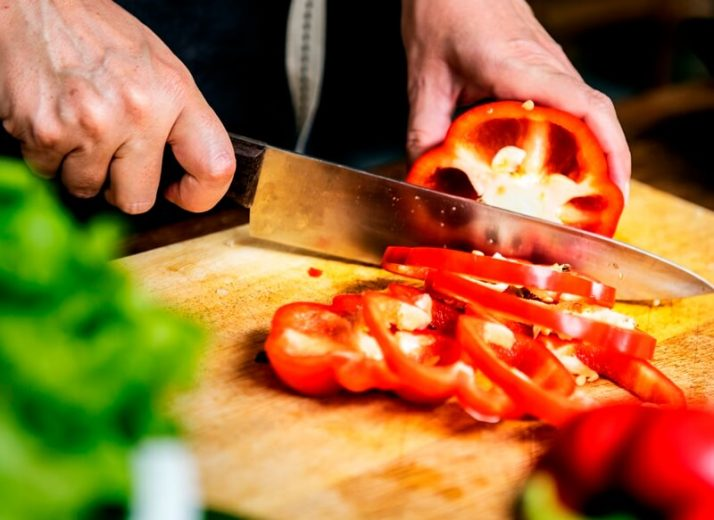 34 High Protein Vegetables You Probably Already Eat; hand with knife cutting bell pepper