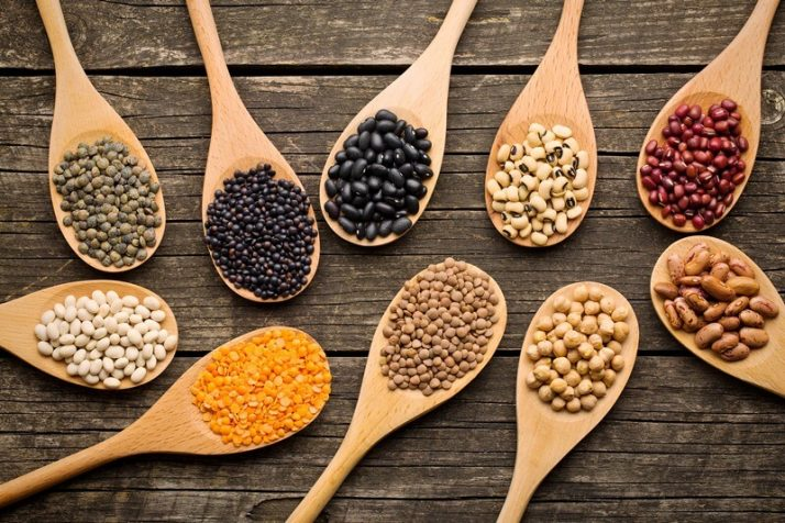 34 High Protein Vegetables You Probably Already Eat; various dried legumes in wooden spoons
