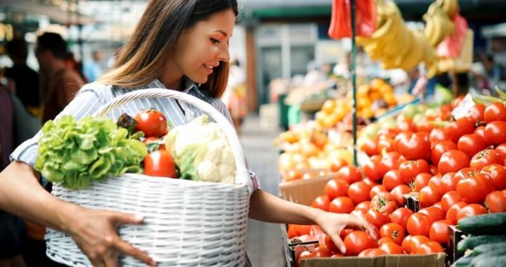 34 High Protein Vegetables You Probably Already Eat; woman at marketplace buying vegetables