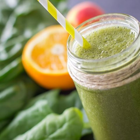 Blended green smoothie with orange and spinach