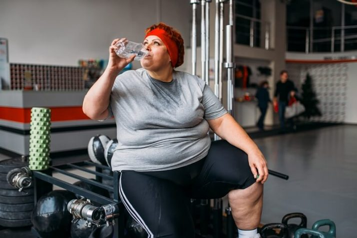 How Much Is Too Much Protein? What No One Is Telling You; Fat woman drinks water after training in gym