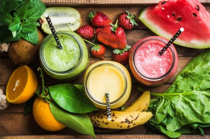 Freshly blended fruit green smoothies of various colors, watermelon, strawberry, banana, orange, kiwi