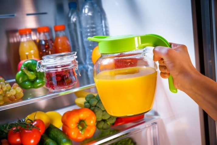 How To Store Smoothies 11 Ways (Fridge, Freezer, How Long); Woman takes the Orange juice from the open refrigerator