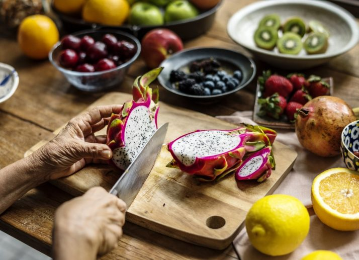 Guide To Fruit: Facts, Benefits, Tutorials, Recipes & Videos; Closeup of hand with knife cutting dragon fruit
