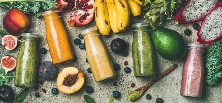 Guide To Fruit: Facts, Benefits, Tutorials, Recipes & Videos; Colorful smoothies in bottles with fresh fruit, copy space