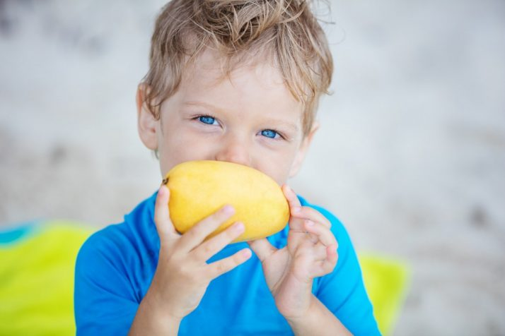 Guide To Mangos: Facts, Benefits, Tutorials, Recipes & Videos; Cute little boy with mango fruit on beach