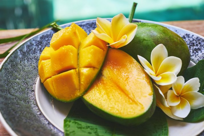 Guide To Mangos: Facts, Benefits, Tutorials, Recipes & Videos; Fresh mango on a wooden tabel with tropical background. Soft focus.