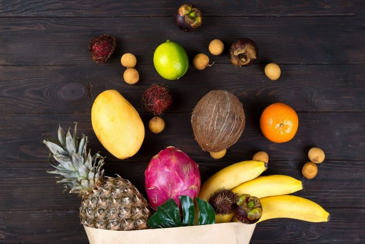 Guide To Fruit: Facts, Benefits, Tutorials, Recipes & Videos; Paper bag of different healthy tropical fruits on dark wooden background. Top view