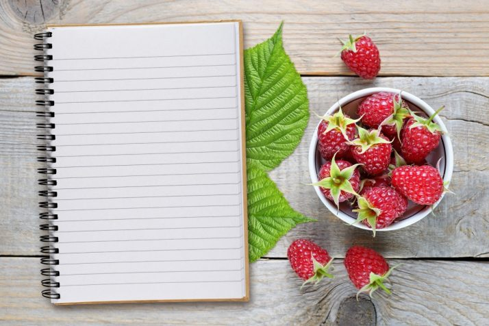 Guide To Fruit: Facts, Benefits, Tutorials, Recipes & Videos; Raspberry and recipe book on wooden table top view
