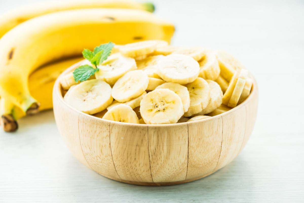 62 Whole Foods Smoothie Fillers To Keep You Going For Hours; Raw yellow banana slices in wooden bowl