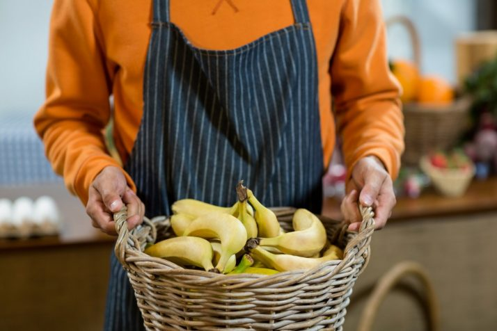 Complete Guide To Bananas: Facts, Benefits, Tutorials, Recipes & Videos; Vendor holding a basket of bananas