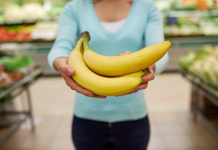 Complete Guide To Bananas: Facts, Benefits, Tutorials, Recipes & Videos; woman with bananas at grocery store