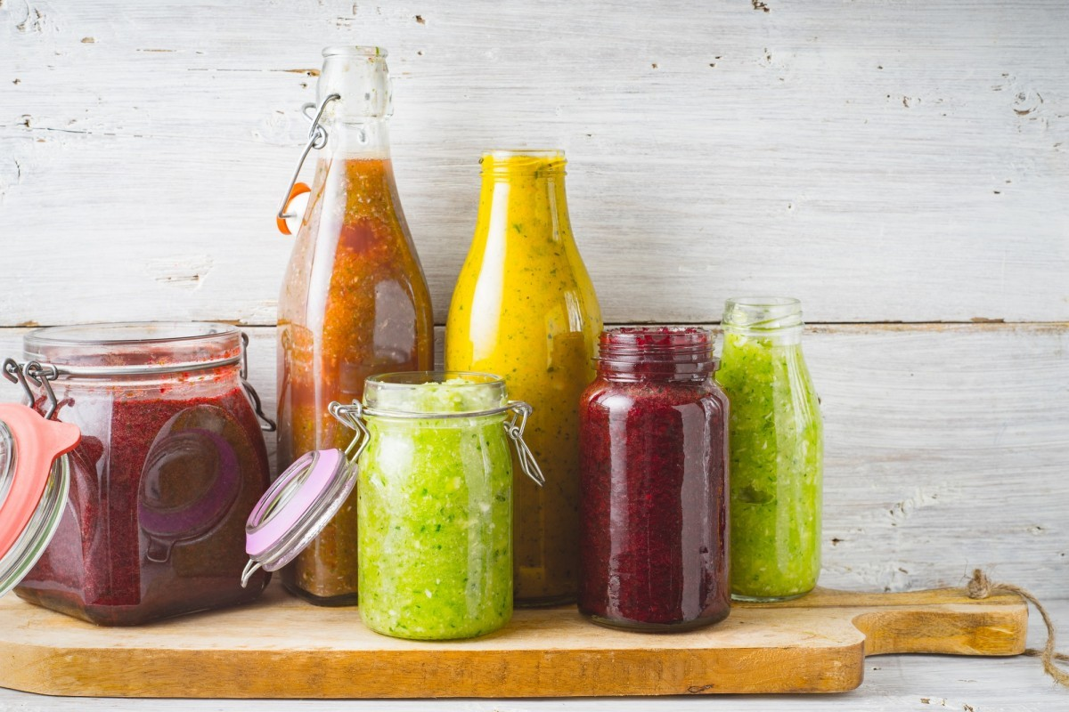 Smoothie Bottles and jar with different smoothie on the wooden board horizontal