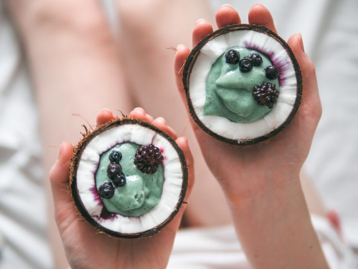 How To Make A Blue Smoothie 3 Ways: With & Without Spirulina ; Two coconut half spirulina smoothie in woman hands
