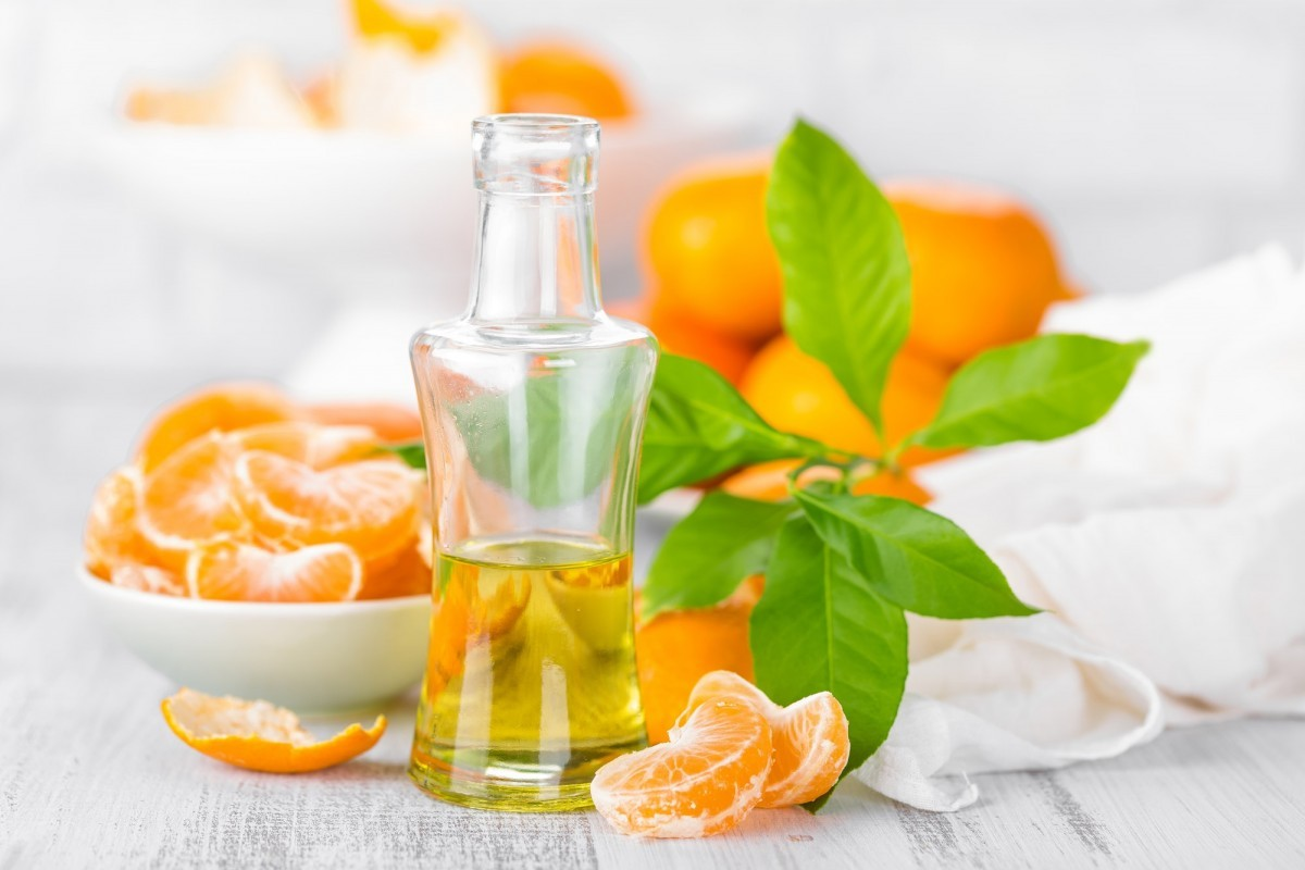 200+ Smoothie Ingredients Shopping List Printable; Tangerines with leaves and bottle of essential citrus oil on a white background