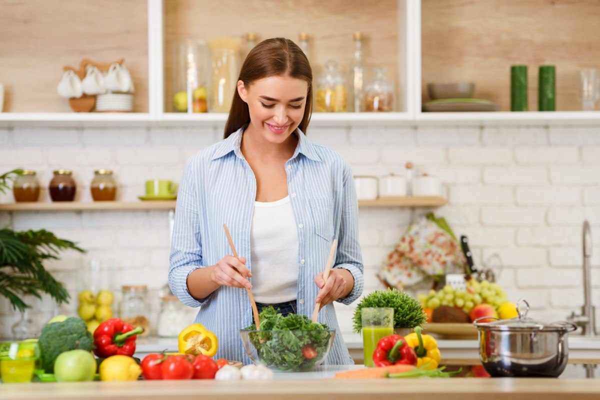3 Vegetables That Provide ALL Your Essential Nutrients (With Only 450 Calories); Healthy Eating. Woman Mixing Fresh Salad In Kitchen