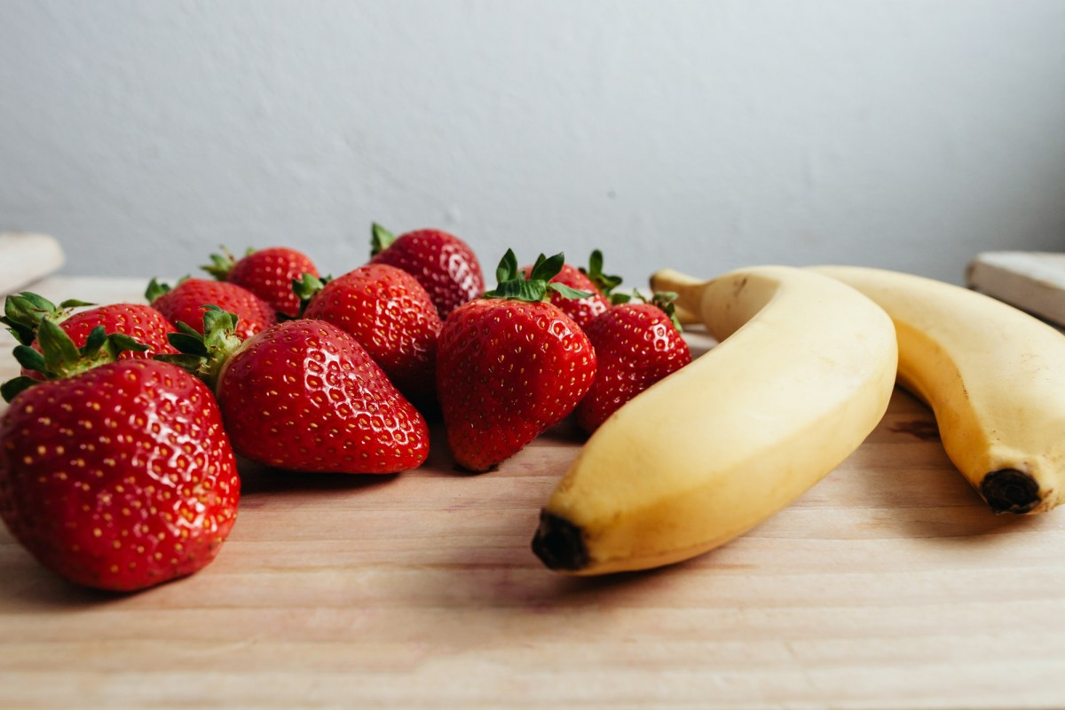 strawberry banana fruits on wood table; Is A Banana A Berry? I Reveal The Truth