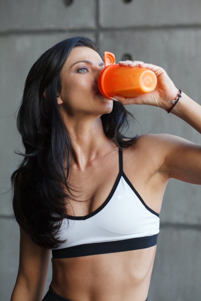 close up portrait of drinking sportswoman in gym
