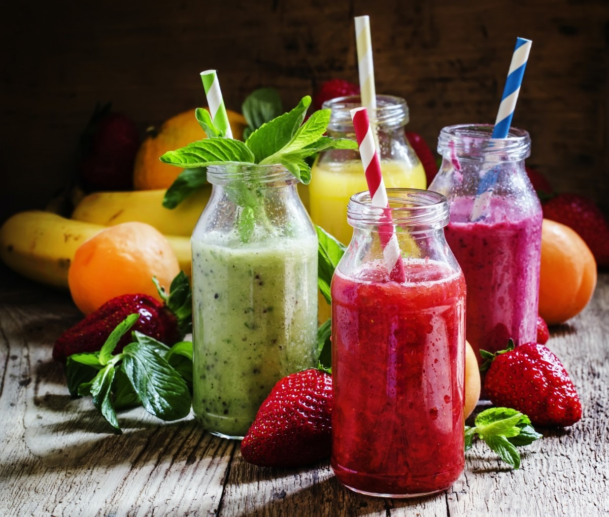 Fruit smoothies with colored straws in glass bottles