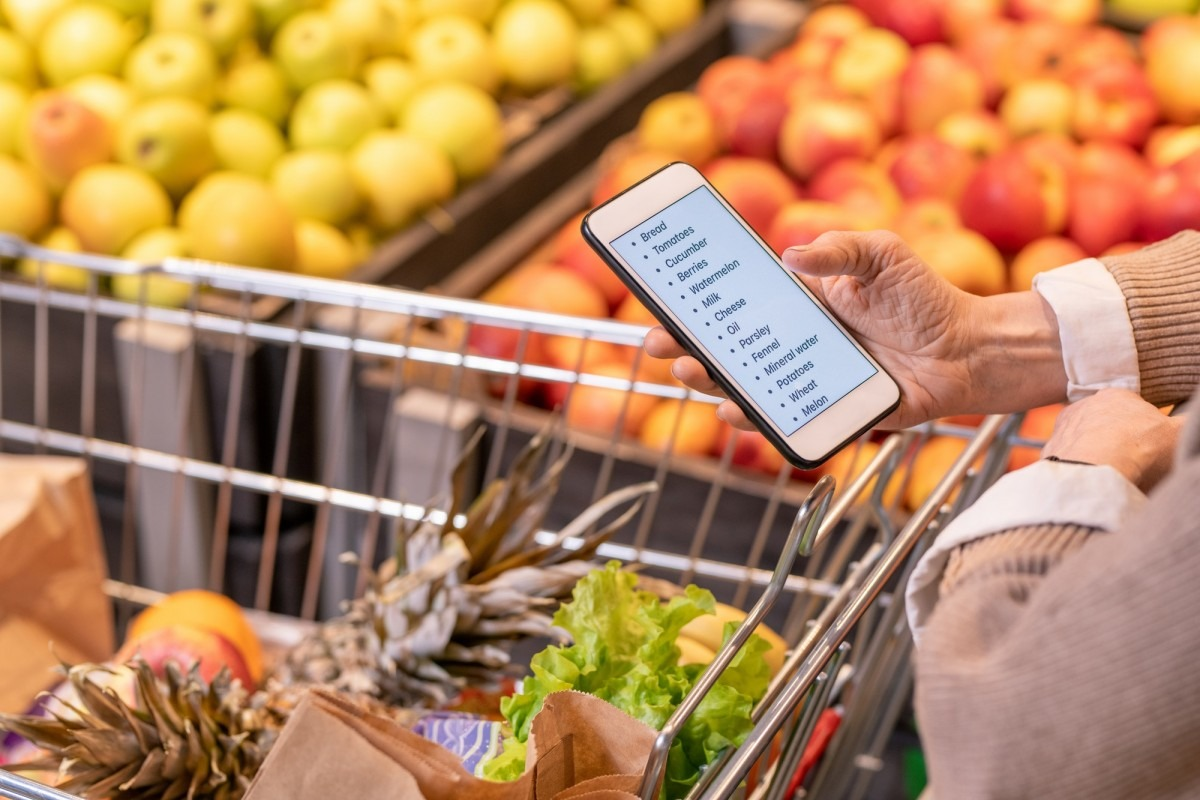 Hands of contemporary aged woman looking through shopping list in smartphone